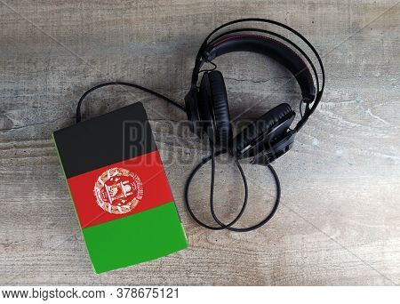 Headphones And Book. The Book Has A Cover In The Form Of Afghanistan Flag. Concept Audiobooks. Learn