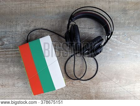 Headphones And Book. The Book Has A Cover In The Form Of Bulgaria Flag. Concept Audiobooks. Learning