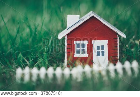 Red Wooden House Model On The Grass