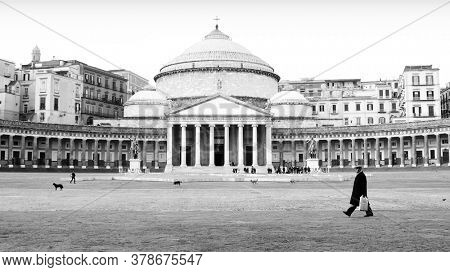NAPLES, ITALY - GENUARY 04, 2008: image black and white a gentleman crosses Square Plebiscito in front of the Pantheon in Naples landmark and monument examples of neoclassical architecture in Italy
