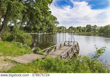 Summer Landscape On The Lake With A Wooden Bridge. Landscape Park In The Palace And Park Ensemble In