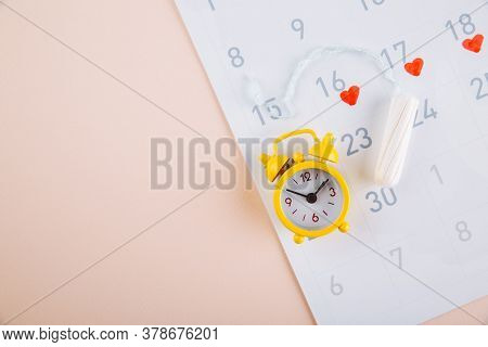 Menstruation Calendar With Yellow Alarm And Daily Sanitary Pads On Pink Background. Woman Critical D