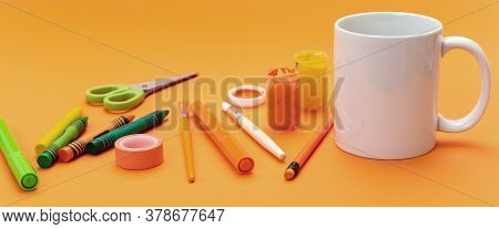 Mug White Color And School Supplies On Orange Background. Kids Soft Drink