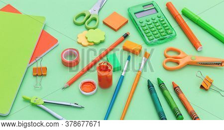 School Supplies On Green Color Background, View From Above