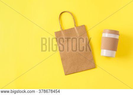 Mockup Of Kraft Paper Shopping Bag With Handles On Yellow Surface, Reusable Portable Coffee Mug For
