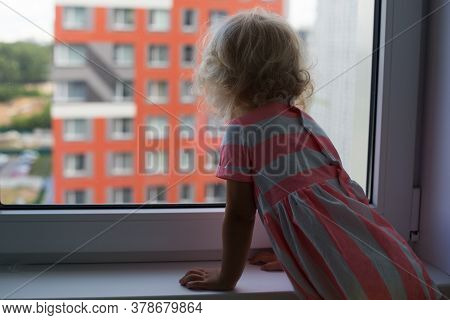 Small Curly Girl With Blond Hair Looking Outside From The Window In Multistory Neighbourhood