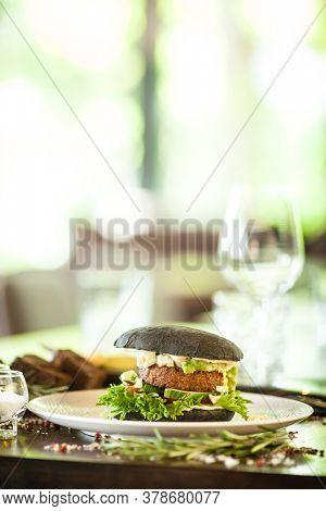 Vegan burger. Black bun, tofu-avocado salad, mayonnaise, cucumber, tomato, fresh salad. Delicious healthy hamburger food closeup served on a table for lunch in modern cuisine gourmet restaurant