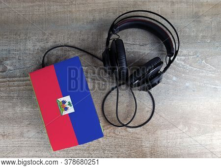 Headphones And Book. The Book Has A Cover In The Form Of Haiti Flag. Concept Audiobooks. Learning La