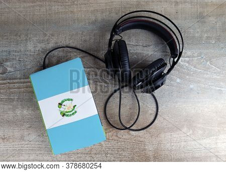 Headphones And Book. The Book Has A Cover In The Form Of Guatemala Flag. Concept Audiobooks. Learnin
