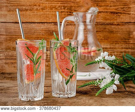 Grapefruit Infused Water With Tonic And Rosemary On Wooden Background. Copy Space