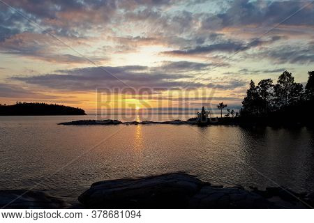 The Sun Goes Over The Horizon, A Beautiful Sunset Over The Lake, Clouds In The Blue Sky. Horizontal