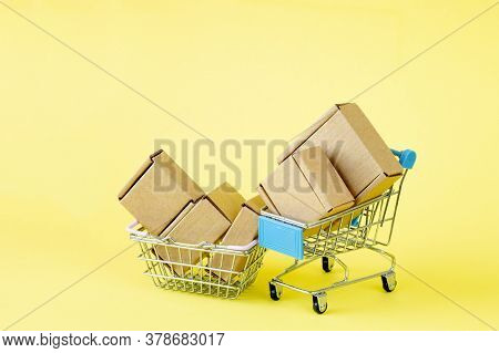 Paper Shopping Bags In A Shopping Cart On Yellow Background, Concept Online Shopping.