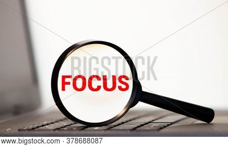 Focus Word Through A Magnifying Glass. Magnifying Glass Search Concept. Isolated On White Background