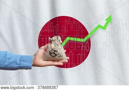 The Concept Of Economic Growth In The Country Japan. Hand Holds A Bag With Money And An Upward Arrow