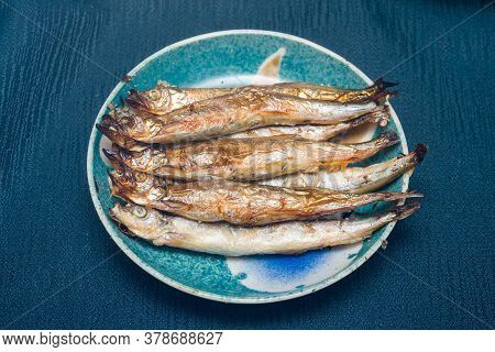 Stacked Several Grilled Capelin On A Light Blue Plate