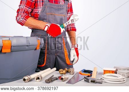 Worker, Service Man Holding Adjustable Wrench And Different Tools, Equipment.