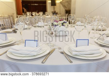 Stylishly Served Banquet Table With Personalized Cards. Beautiful Flowers, Empty Plates On A White T
