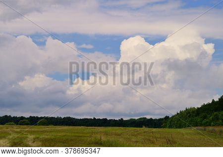 Big Storm Cloud On The Blue Sky Above The Field In The Countryside, Away From The Bustle Of The City