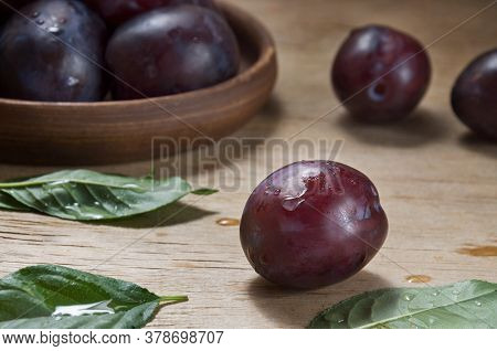 Ripe Blue Plum With Drops On A Wooden Table Against The Background Of A Ceramic Plate With Plums. Th