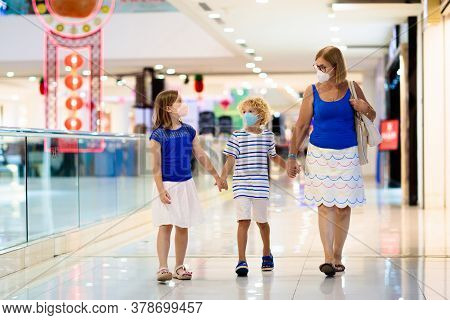 Family Wearing Face Mask In Shopping Mall In Asia. Mother And Children Wear Facemask During Coronavi