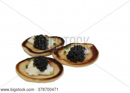 Close Up Of Three Russian Pancakes Or Blini With Sour Cream And Black Sturgeon Caviar On A Plate