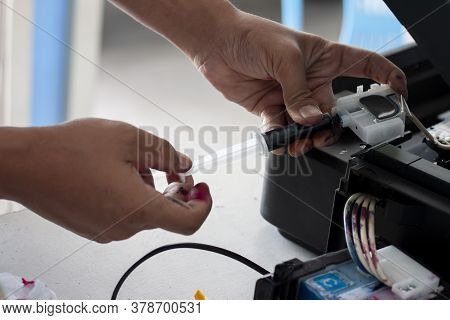 The Technician Is Repairing The Printer. By Sucking Out The Paint To Chase Bubbles.