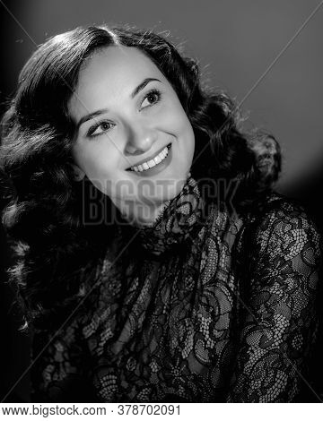 Portrait Of Beautiful Smiling Brunette With Long Wavy Hair. Image In Black And White Conversion