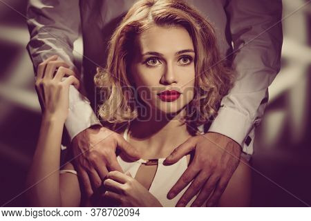 Portrait Of Young Gorgeous Blonde And Male Hands Hugging Her, Image With Vintage Toning