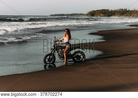Beautiful Single Girl With A Motorbike On The Beach Meets The Sunset. Stylish Woman With A Bike By T