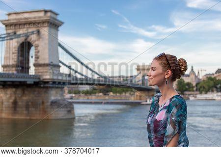 Young Woman Daydreaming At Szechenyi Chain Bridge At Budapest, Hungary