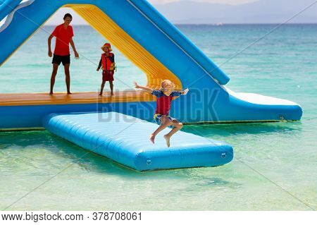Kids On Trampoline On Tropical Sea Beach.