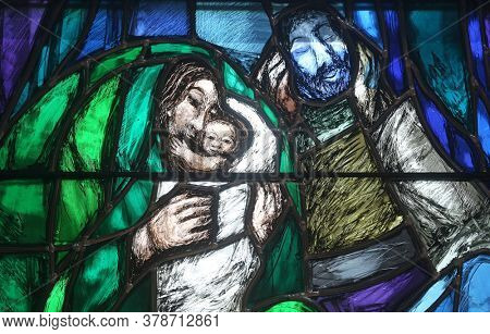 PIFLAS, GERMANY - JUNE 07, 2015: God begins salvation in this world through His Son Jesus Christ, detail of stained glass window by Sieger Koder in St. John church in Piflas, Germany