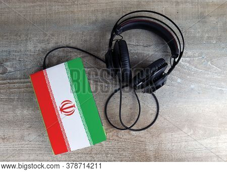 Headphones And Book. The Book Has A Cover In The Form Of Iran Flag. Concept Audiobooks. Learning Lan