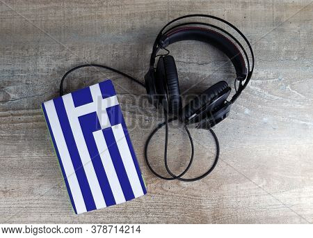 Headphones And Book. The Book Has A Cover In The Form Of Greece Flag. Concept Audiobooks. Learning L