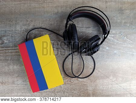 Headphones And Book. The Book Has A Cover In The Form Of Colombia Flag. Concept Audiobooks. Learning