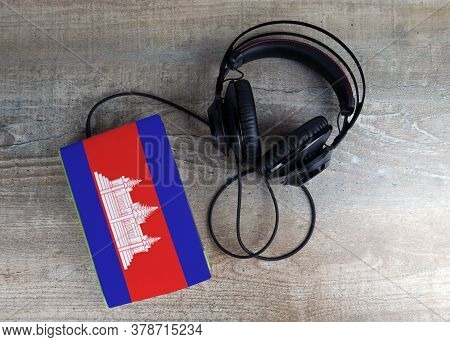 Headphones And Book. The Book Has A Cover In The Form Of Cambodia Flag. Concept Audiobooks. Learning