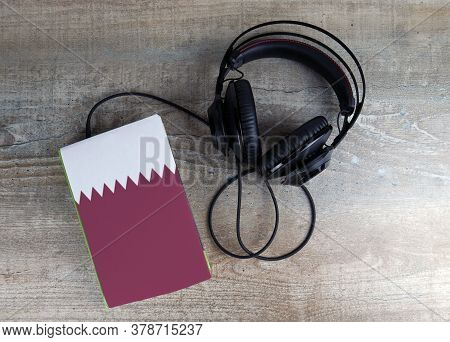 Headphones And Book. The Book Has A Cover In The Form Of Qatar Flag. Concept Audiobooks. Learning La