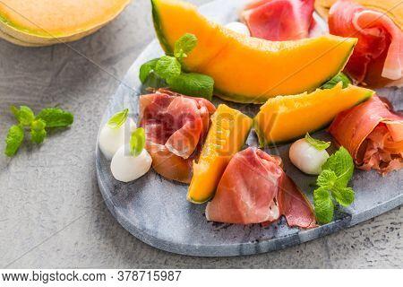 Traditional Italian appetizer - Prosciutto with cantaloup melon, mozzarella, basil and mint