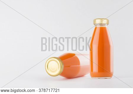 Orange Carrot Vegetables Juices In Glass Bottles With Gold Empty Cap For Label Mock Up On White Back