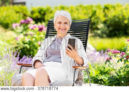 technology, old age and people concept - happy smiling senior woman with smartphone resting at summer garden