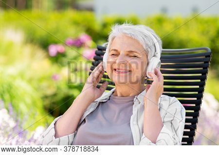 old age, retirement and people concept - happy senior woman with headphones listening to music at summer garden