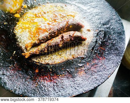 Frying Two Sardine In A Frying Pan.the Pan Has Dark Color In Its Background And The Fish Is Well Mad