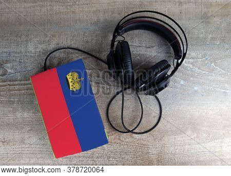 Headphones And Book. The Book Has A Cover In The Form Of Liechtenstein Flag. Concept Audiobooks. Lea