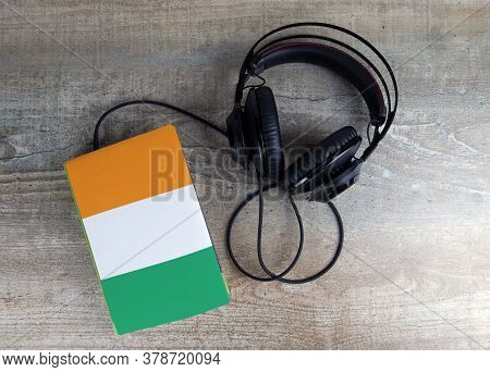 Headphones And Book. The Book Has A Cover In The Form Of Ivory Coast Flag. Concept Audiobooks. Learn