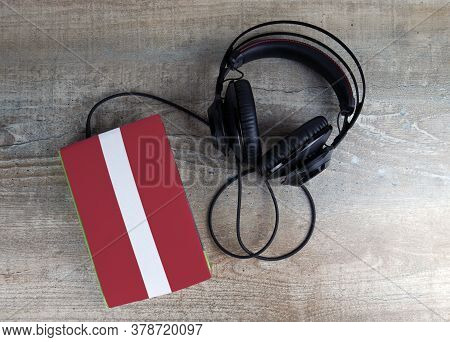 Headphones And Book. The Book Has A Cover In The Form Of Latvia Flag. Concept Audiobooks. Learning L