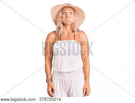 Middle age fit blonde woman wearing summer hat puffing cheeks with funny face. mouth inflated with air, crazy expression.