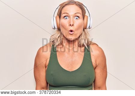 Middle age caucasian blonde woman listening to music using headphones scared and amazed with open mouth for surprise, disbelief face