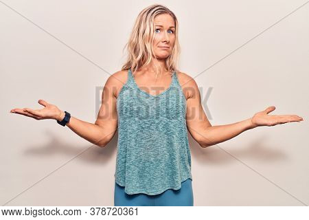Middle age caucasian blonde woman wearing sportswear clueless and confused with open arms, no idea concept.