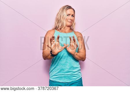 Middle age caucasian blonde woman wearing sports clothes over pink background disgusted expression, displeased and fearful doing disgust face because aversion reaction. with hands raised