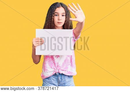 Cute hispanic child girl holding blank empty banner with open hand doing stop sign with serious and confident expression, defense gesture